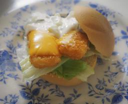 Foto van een broodje visfilet met remouladesaus en een plakje cheddar kaas
