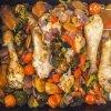 Foto van een ovenschotel met veel groenten en kippenpoten